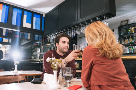 Romantic date. Low angle of happy vigorous couple drinking wine and gossiping Stock Photo