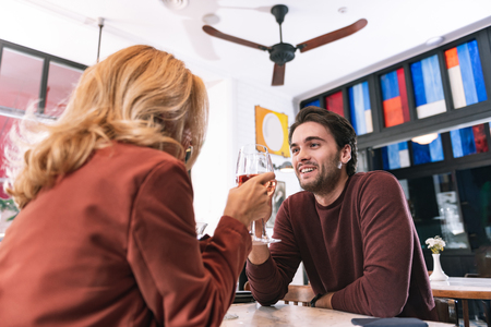 Romantic evening. Low angle of nice positive couple drinking wine and speaking Stock Photo