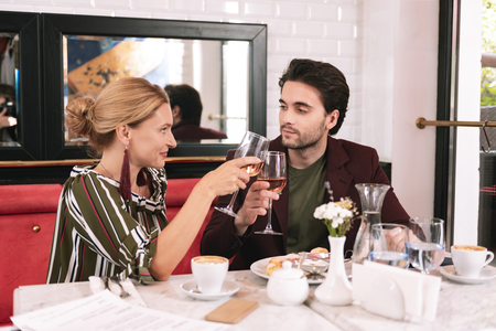 Cunning plans. Charming pretty couple sitting at restaurant and relishing wine Imagens