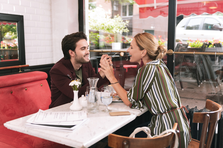 Give me. Sincere positive couple sitting at restaurant and taking hands