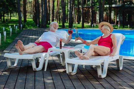 Retired couple. Couple of retired people feeling unbelievable while having rest lying on deck chair