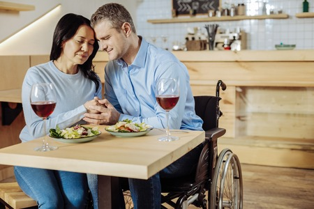 Love in the air. Disabled sensative man hugging a woman while having a date Stock Photo