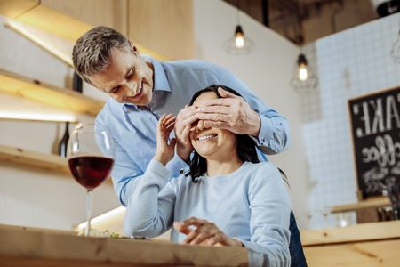 Positive mood. Smiling lovely man closing womans eyes while having dinner in a restaurant
