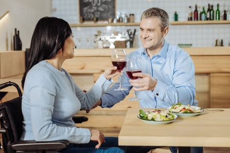 Delicious food. Paralyzed brunette lady having dinner with a man while drinking wine