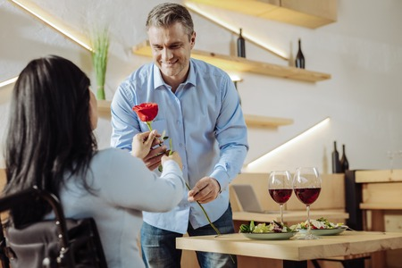 Red rose. Cheerful handsome man presenting a flower to a woman while having dinner in a restaurant Imagens