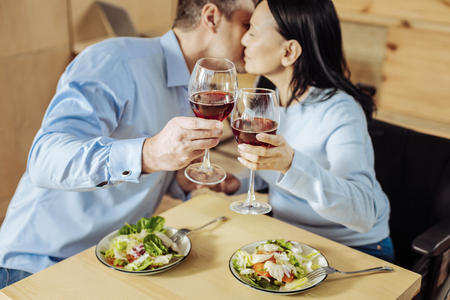 Calm atmosphere. Pleasant happy husband and wife having dinner and drinking wine in a cafe Stock Photo