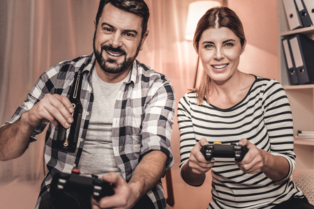Day off. Gorgeous relaxed man and woman playing a video game and drinking beer
