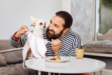 Care and share. Caring loving owner of white cute funny dog sharing his piece of dessert with his dog