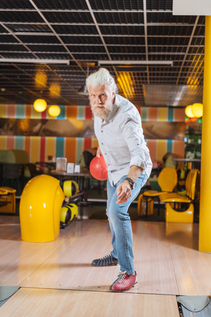 Favourite activity. Nice pleasant man visiting a bowling club while enjoying his weekend Stock Photo