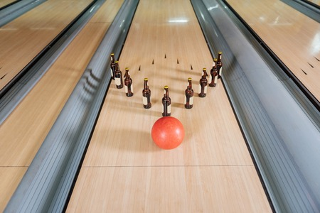 This will be strike. Top view of a bowling ball approaching bottles of beer