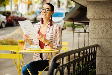 Happy person. Cheerful young person enjoying her lunch time and smiling while sitting outdoors with a menu in her hands