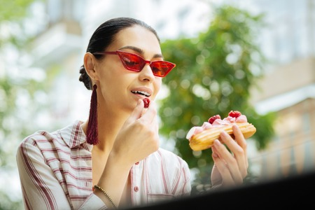 Eating raspberries. Cheerful beautiful visitor of a cafe holding a delicious eclair and eating raspberries on the top of it Reklamní fotografie
