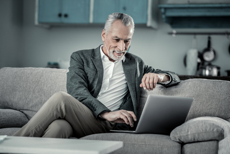 Be positive. Cheerful grey-haired freelancer sitting on cozy sofa while reading news with pleasure