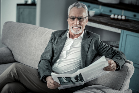 Look at me. Delighted mature man keeping smile on his face while going to read newspaper