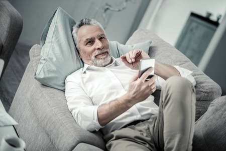 Answer creation. Relaxed gray-haired man holding telephone in left hand while having rest at pause