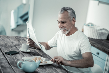 So tasty. Cheerful pensioner eating healthy food while reading news