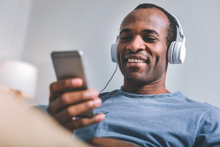 Modern life. High-spirited joyful man sitting in headphones while listening to the music