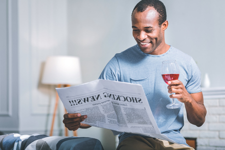 Good news. Smiling handsome man reading a newspaper while drinking wine Stock Photo