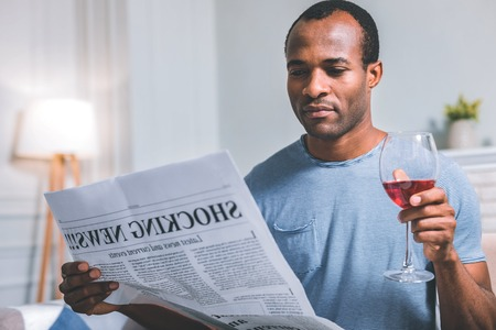 Evening rest. Tired calm man reading a newspaper while drinking red wine Stock Photo