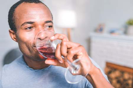 Good wine, Attractive pleasant man holding a glass of wine while aside