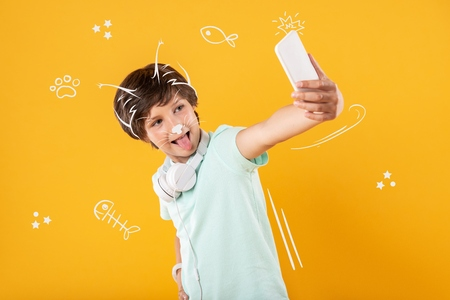 Funny selfie. Cheerful funny teenager standing with a modern smartphone and showing his tongue while taking selfies