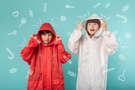 Rainy day. Emotional children wearing convenient colorful raincoats and looking ready for bad weather Stock Photo
