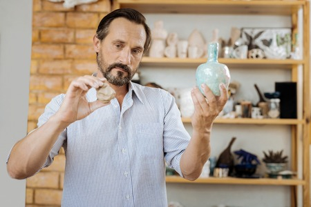One more. Dark-haired creative handicraftsman looking at nice ceramic vase while making one more