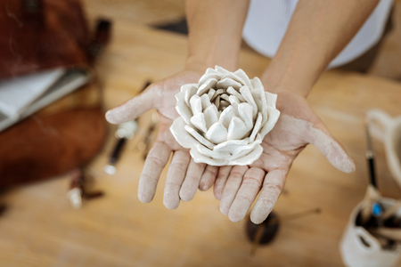 Nice flower. Top view of nice earthenware decorative flower in hands of creative inspired handyman