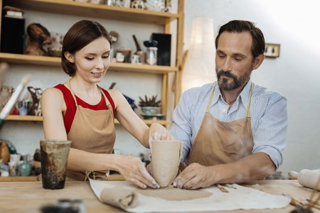 Female potter. Bearded man wearing striped shirt looking at female potter working actively in workroom Stock Photo