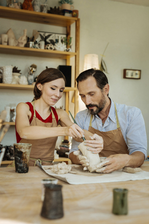 Making clay pot. Bearded dark-haired man feeling useful while helping his wife in making clay pot