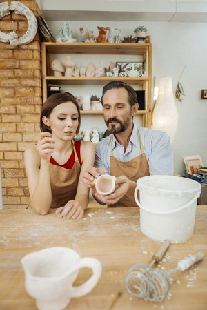 Favorite activity. Couple of experienced skillful potters doing their favorite activity together in workroom 写真素材 - 107104498