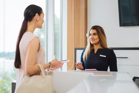 tengo una buena mujer atractiva hablando con la recepcionista mientras que tener cita en un salón de belleza