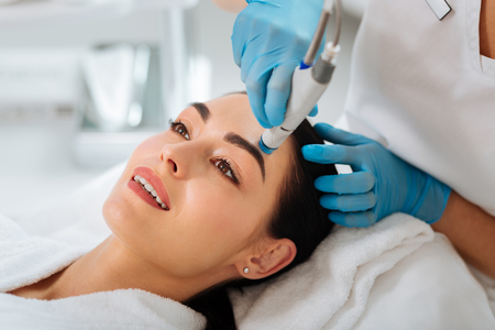 Rejuvenation of skin. Delighted nice woman smiling while enjoying hydrafacial procedure Stock fotó