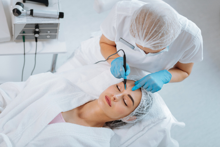 Professional cosmetology. Smart skilled cosmetologist removing a mole while working in the clinic