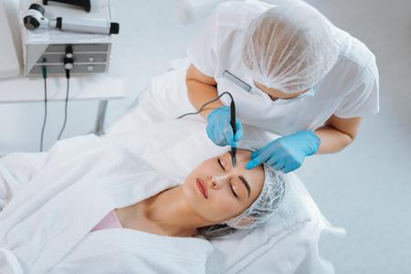 Professionelle Kosmetologie. Intelligente qualifizierte Kosmetikerin, die einen Maulwurf entfernt, während sie in der Klinik arbeitet
