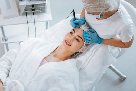 Aesthetic look. Delighted positive woman smiling while feeling happy about the cosmetology procedure Stockfoto