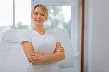 Cosmetóloga profesional. Mujer feliz alegre de pie con las manos cruzadas mientras trabajaba como cosmetóloga Foto de archivo