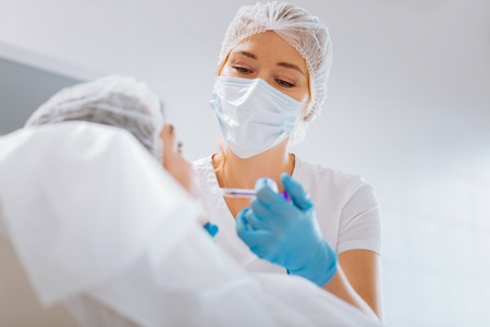 Absolutely sterile. Smart professional female cosmetologist wearing a mask while doing an injection for her client