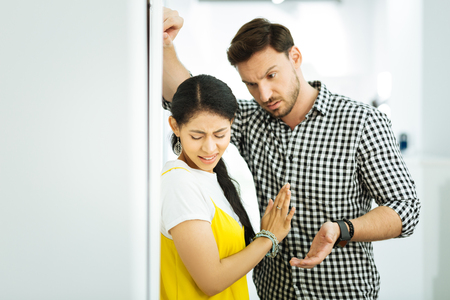Leave me alone. Serious man leaning to a scared girl and looking pushy while the girl trying to escape from him Stock Photo