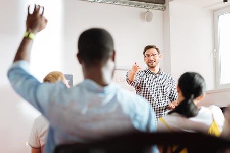 Sí tú. Orador amistoso alegre que lleva a cabo un taller de negocios y apunta a un estudiante levantando su mano