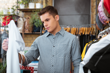 White clothes. Calm serious young man looking attentively at the white T shirt in his hand and thinking about buying it