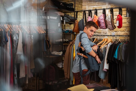 Hiding clothes. Quick professional thief hiding new clothes into his big backpack while stealing in a fashionable shop Stock Photo