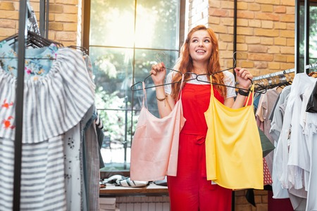 Taking two. Excited young woman looking happy and smiling while visiting a nice shop and buying two wonderful blouses