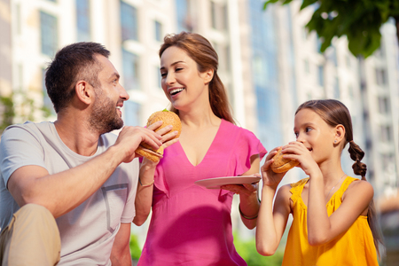 Tasty food. Joyful happy family eating tasty hamburgers while enjoying their picnic
