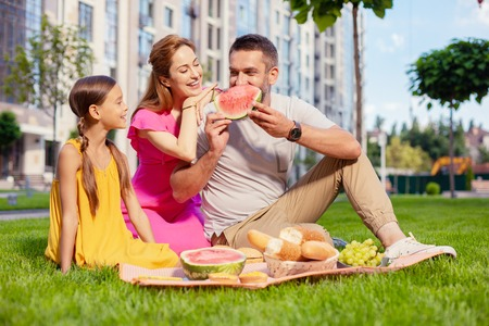 Family picnic. Joyful delighted man looking at his daughter while eating watermelon