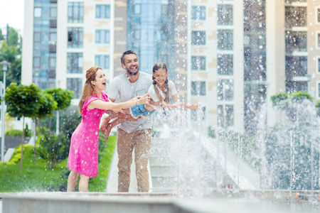 Fun times. Delighted happy parents playing with their daughter while standing near the fountain