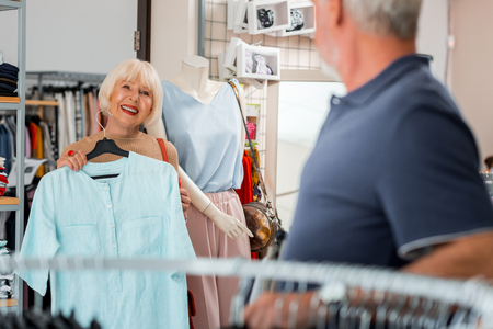 Best choice. Waist up of delighted grey haired woman keeping recently chosen dress at her chest while looking at her husband and expressing satisfaction with future purchase Stock Photo