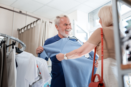 Looking great. Positive elderly woman giving stylish pullover to her cheerful husband while being pleased with the choice