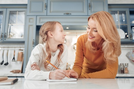 Family day. Cheerful blonde woman leaning on table while helping her daughter to study Stock Photo
