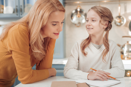 Need your help. Attentive woman standing near her kid while checking homework in copybook